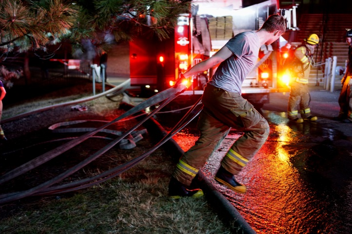 Firefighter starts to bring hoses in after the fire was put out. (Photo by Heather Kim)