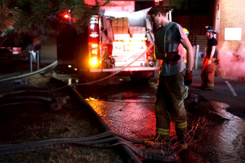 Firefighter drops hose on the ground in the puddle of water leaking from the other hoses. (Photo by Heather Kim)