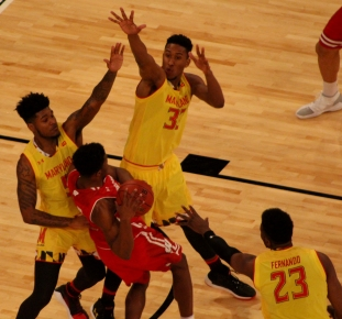 Joshua Tomaic (33), Dion Wiley (5) and Fernando (23) block a Wisconsin player from shooting.